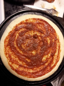 Spread the sauce with a ladle or spoon leaving some bare dough at the edges.